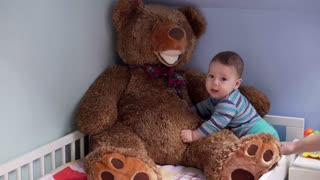 Little baby boy playing in bed with big toy bear