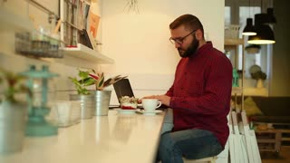 Male man finishing work on laptop and relaxing in cafe
