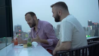 Man after alcohol arguing with each other on the building's roof