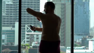 Man applying antiperspirant on armpit by window, slow motion shot at 240fps