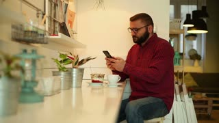 Man browsing internet on smartphone in the restaurant