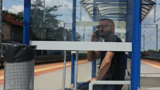 Man chatting on cellphone while sitting on the train stop and waiting for arrival