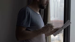 Man drinking coffee and reading newspaper in his apartment