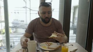 Man drinking hot coffee and eating sandwich for breakfast