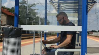 Man finish using laptop on the platform and leaving the stop