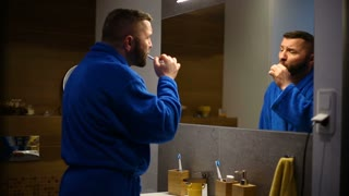 Man in blue bathrobe standing in fron of the mirror and brushing his teeth