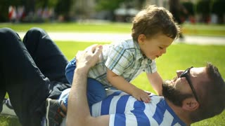 Man lying with his son on the grass in the park and relaxing