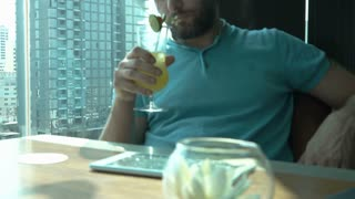 Man sitting in pub and looks very drunk while drinking alcoholic drink
