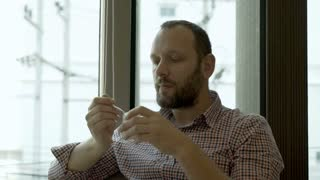 Man sitting in the cafe next to the window and eating yoghurt