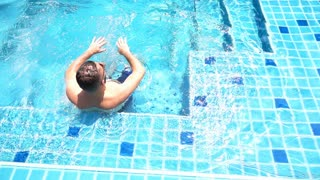 Man sitting in the pool and relaxing, slow motion shot at 240fps