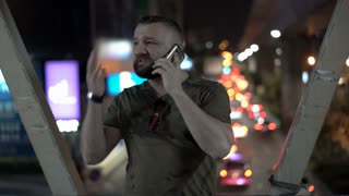 Man standing at night in the city and looks angry while speaking on cellphone