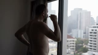 Man standing in fron of the window and brushing his teeth