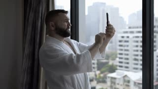 Man standing in his hotel room and captures view from window on smartphone