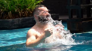 Man standing in the pool and splashing water on himself, slow motion shot at 240fps