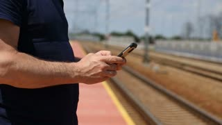 Man standing next to the railroad and texting messages on smartphone