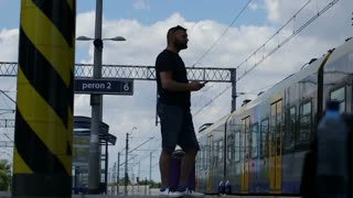 Man standing on platform and using smartphone while waiting for his train