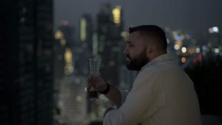 Man standing on the balcony at night and drinks beer