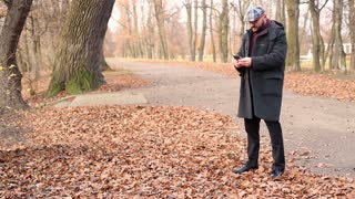 Man texting cellphone in autumn park