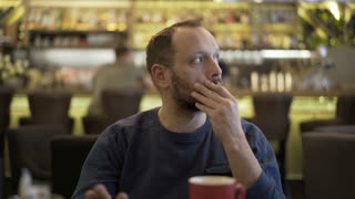 Man waiting in the cafe for someone and looks annoyed