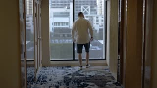 Man walking in hallway and waiting for elevator