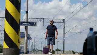 Man walking on the platform and looks irritated while waiting for train