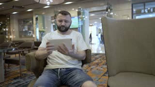 Man watching funny videos on tablet in the hotel's cafe