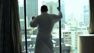 Man wearing bathrobe and dancing in fron of the window, slow motion shot at 120fps