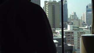 Man wearing bathrobe and walking to the window