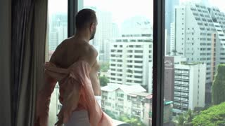 Man wearing towel and takes his shirt off while admiring the view, slow motion shot at 240fps