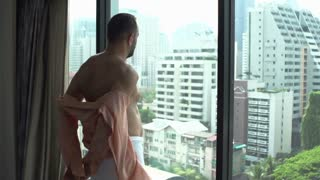Man wearing towel and takes his shirt off while admiring the view