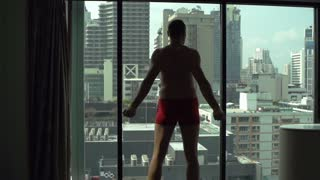 Man wearing underwear and stretching muscles in fron of the mirror, slow motion shot at 120fps