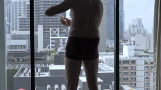 Man wearing underwear in his hotel room and using deodorant