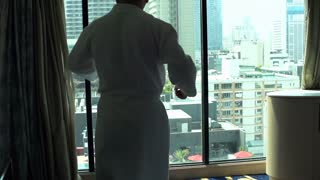 Man wearing white robe and dancing in his apartment in front of the window