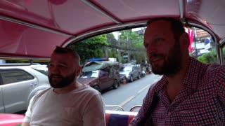 Men riding a tuktuk and looking happy, slow motion shot at 240fps