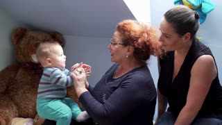 Mother and grandmother play with kid ,keeps his hand and play