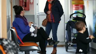 Mother breast feeding her newborn baby and sitting in waiting room in the hospital