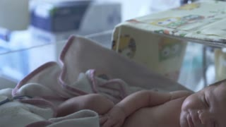 Mother covers her newborn baby with blanket while lying in incubator