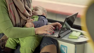 Mother holding sleeping baby and using PC in the train