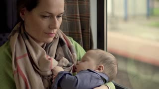 Mother holding sleeping baby and using phone in the train