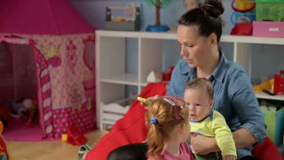 Mother talking on cellphone and spend time with children