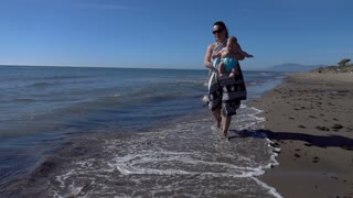 Mother with baby walking on the beach , super slow motion
