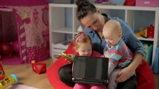 Mother with children watching something on laptop