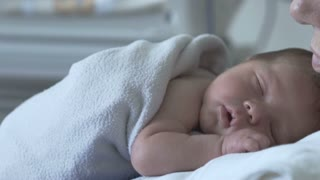 Newborn baby smiles while sleeping on his mother in the hospital