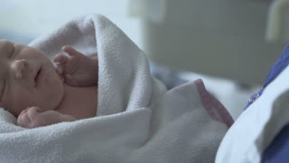 Newborn baby wakes up and starts to move while being covered in blanket