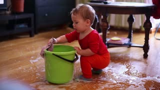 Nice baby lovely boy playing with spilled water on the floor at home