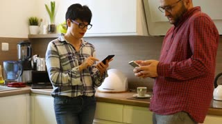 Pair standing in the kitchen and using smartphones while speaking with each
