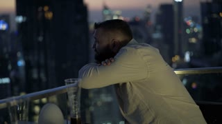 Pensive man leaning on balcony and admire the view of city at night