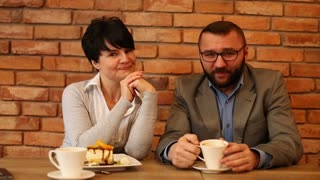 Portrait of happy couple businesspeople sitting by table in cafe