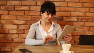 Portrait of happy woman with tablet computer in cafe