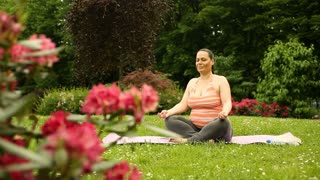 Pregnant woman answers cellphone while doing yoga in the garden